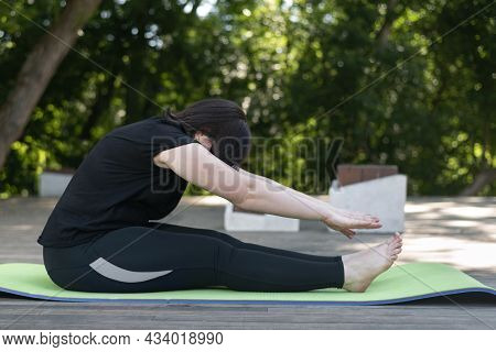 Young Beautiful Flexible Girl Makes A Lean Forward With Her Hands From A Sitting Position. Side View
