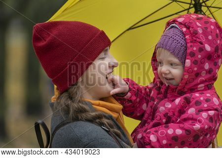 Portrait Of Mom And Baby Under Yellow Umbrella In Park. Mom And Little Daughter Fooling Around