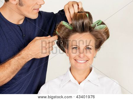 Portrait of female customer with hairstylist curling her hair at parlor