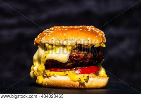 Detail Of Fresh Tasty Beef Cheeseburger With Melted Cheese Isolated On Black Background