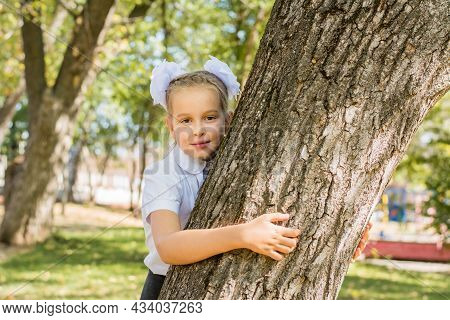 A Cute Schoolgirl With White Bows Stands By A Tree In A Sunny Autumn Park. First Grade On September