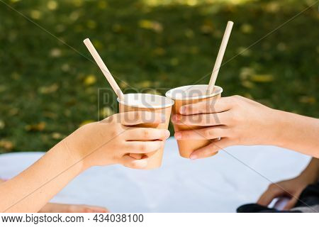 Two Children's Hands Are Holding Eco-friendly Cups And Tubes With Apple Juice At A Picnic In The Par