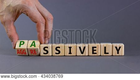 Passively Or Aggressively Symbol. Businessman Turns Cubes And Changes The Word Passively To Aggressi