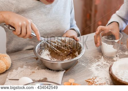 Preparing To Celebrate Halloween And Preparing A Treat. Children Whisk Gingerbread Dough With A Whis