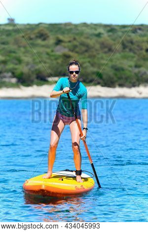 Young Active Girl Sup Board With A Paddle In Hand - Front View - The Calm Surface Of The Blue Sea