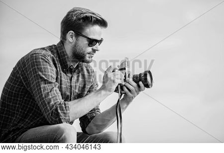 Blogger Shooting Vlog. Handsome Blogger Guy Traveler Retro Camera. Manual Settings. Photojournalist