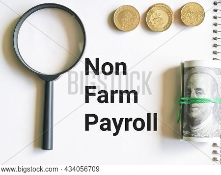 Business And Finance Concept. Selective Focus Notebook Written Non Farm Payroll With Coins,fake Mone