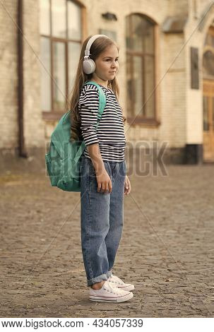 Commit To Travel. Little Girl Carry Backpack Wearing Headphones Outdoors. Summer Travel. Vacation Tr
