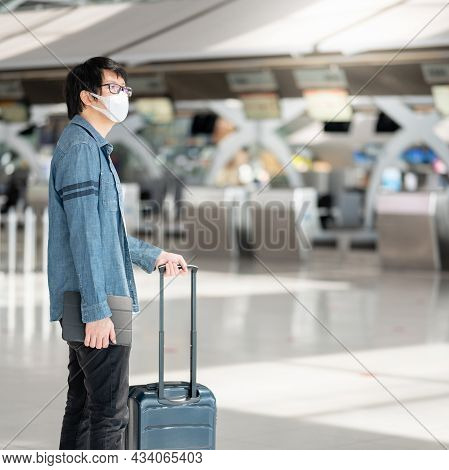 Asian Man Tourist Wearing Face Mask Carrying Suitcase Luggage At Check-in Counter In Airport Termina