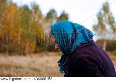 Defocus Portrait Of Russian Grandmother Senior Old Woman Standing In Yellow Autumn Park. Old Women I