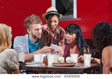 Friends Eating And Looking At Phone