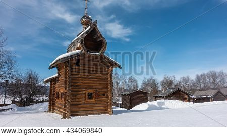 The Old Church Is Built Of Unpainted Logs. Small Windows With Shutters. Domes Against The Blue Sky.