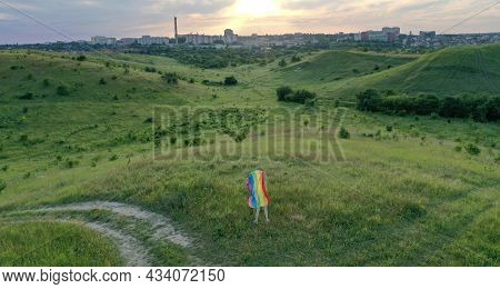 Bisexual, Lesbian, Blonde Woman, Transgender Holds Lgbt Flag In White Dress On The Green Hills On A