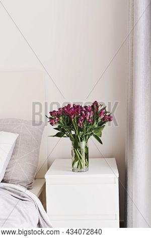 Alstroemeria Flowers In A Vase On A White Bedside Table. Simple And Cozy Bedroom Decor. Minimal Styl