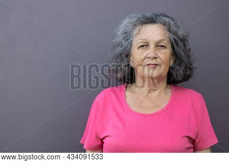 An Elderly Woman With Gray Hair In A Bright T-shirt On A Gray Background Looks At The Camera. Mature