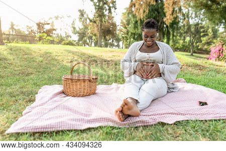 Happy Afro Woman Touching Her Pregnant Belly Doing Heart Shape With Hands In Public Park - Maternity