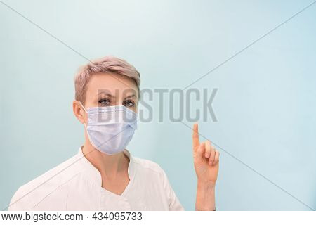 The Medic Points His Finger At A Place Free For Text Or Images. Doctor, Blond Woman With Short Hair.