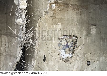 A Partially Wrecked Reinforced Concrete Structure, With Crooked Reinforcing Steel Bars Protruding Ou