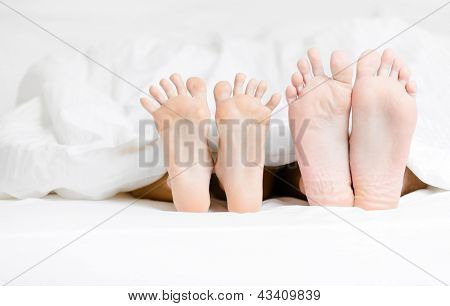 Close up view of two pairs of feet of the couple next to each other in bed