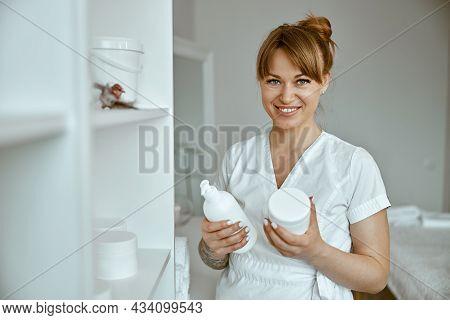 Beautiful Happy Caucasian Female Masseur Is Posing In White Minimalistic Modern Treatment Salon