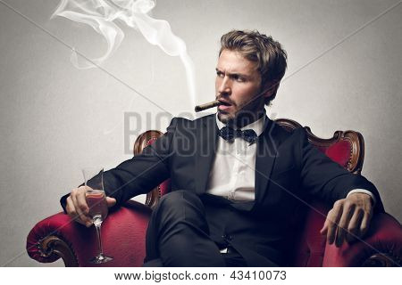 handsome boss sitting on the armchair smokes cigar poster