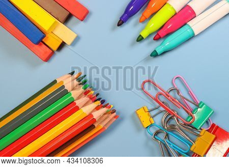 Back to school concept showing colorful pencils, markers, pastels and clips on blue background