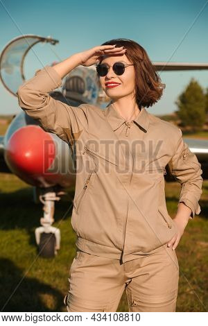 Beautiful confident female pilot poses on the airfield in the background of a fighter jet and light blue sky looking into the distance with a happy smile. Commercial and military aviation.