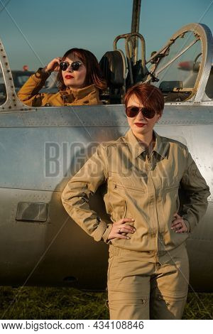 Aviation. Two professional female commercial aviation pilots in uniform and sunglasses posing on the airfield with their fighter jet ready to start their flight.