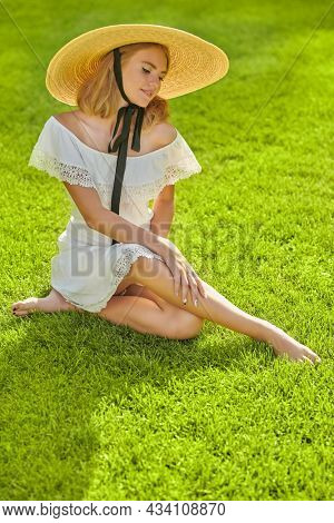 Summer beauty, fashion. Full length portrait of a romantic blonde girl in an elegant white dress and wide-brimmed straw hat, resting on a green lawn. Summer vacation.