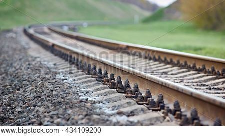 Selective Focus Railway Track Turns And Twists Between Out Of Focus Hills Background. Empty Rounding