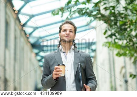 A young successful businessman is walking down the street. Man in a casual wear. Business, freelance and remote work.