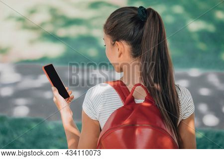 Phone student girl using mobile app online walking outside at park campus for college student vaccine passport. View of black screen for copyspace.