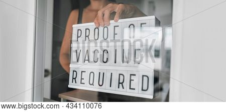 Vaccination proof vaccine passport required for entering store and restaurant as coronavirus restriction. Employee holding notice requirement sign in window of storefront.