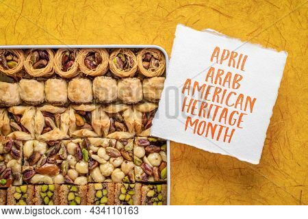 April - Arab American Heritage Month, reminder note with a tin box of traditional Turkish baklava pastry