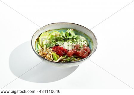 Healthy food - poke bowl with tuna, rice, fresh vegetables and Hawaiian sauce. Hawaiian meal poke bowl with tuna isolated on white background. Dinner for slimming