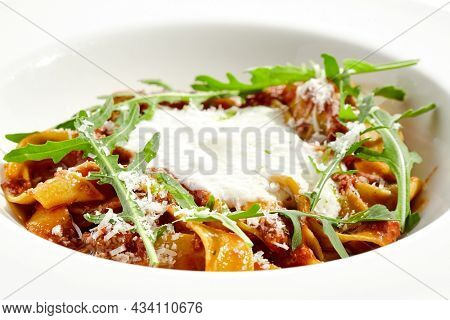Italian pasta pappardelle with bolognese sauce  and parmesan isolated on white background. Pasta tagliatelle with meat ragu and creamy espuma with arugula. Minced beef in tomato sauce with pasta