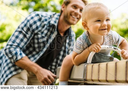 White father smiling while playing with his son at playground outdoors