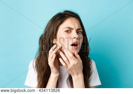 Skin Care. Image Of Worried Teenage Girl Looking In Mirror And Spot A Pimple On Face, Trying Squeeze