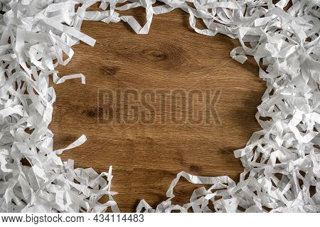 Frame Of Shredded Paper On Wooden Table For Background, Top View Of White Paper Strips Heap. Flat La