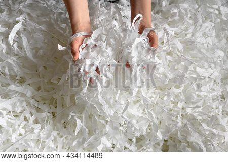 Recycle, Waste, Trash And Ecology Concept. Shredded Paper Heap In Hands, Top View Of Many White Stri