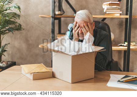 Damaged Package. The Elderly Man At The Table At Home Closed His Eyes, Broken Goods. Postal Delivery