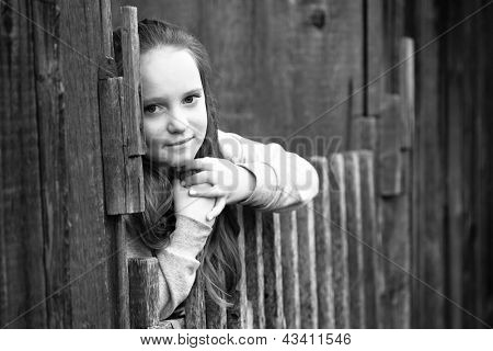 Portrait of teen-girl standing near vintage rural fence, black-and-white photo.