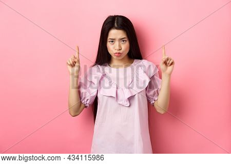 Sad And Moody Asian Girl Look From Under Forehead And Sulking, Pointing Fingers Up And Complaining,