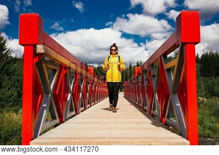 A Young Tourist Girl In A Yellow Jacket With A Backpack Is Walking Along The Red Bridge. A Tourist W