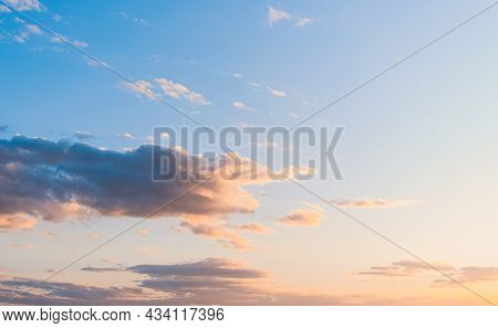 Fluffy Clouds On A Sunset Background With Dramatic Light.