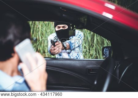 Blurred Soft Images Of Male Criminals Currently Using A Carbine To Rob A Man Which Is Talking Mobie