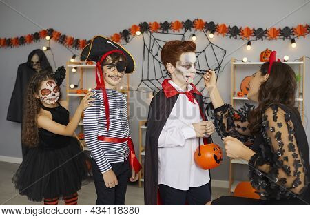 Face Paint Artist Applying Spooky Makeup To Group Of Kids At Fun Halloween Party At Home