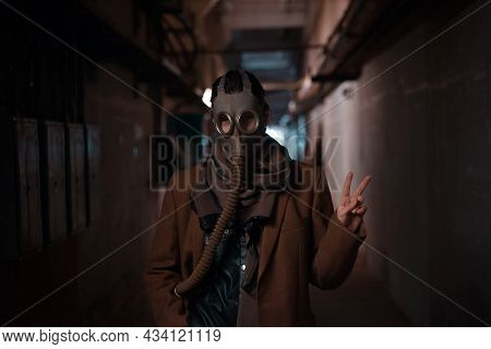 Bleak Future, Environmental Problems, And Pandemics. A Woman In A Bunker. Uses A Gas Mask For Protec