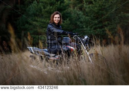 Woman On A Motorbike In Nature. Biker Motorcycle Ride Through The Woods