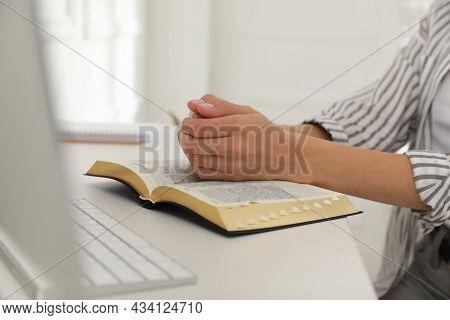 Young Woman Praying Over Bible At Desk, Closeup